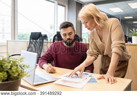 Blond mature businesswoman in casualwear pointing at financial paper while discussing diagrams and charts with her young male colleague