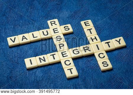 integrity, respect, values and ethics crossword in ivory letters against textured handmade blue paper, moral obligations, conduct and personal devleopment concept