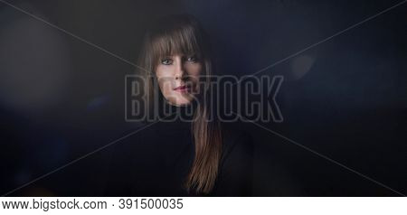 Beauty portrait of attractive young woman looking at camera, serious facial expression. Dark background.