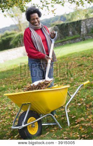 Woman Putting Leaves Into Wheelbarrow