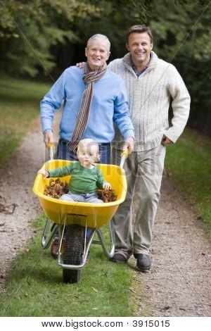 Men Pushing Baby In Wheelbarrow