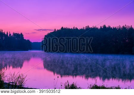 Magical Purple Sunrise Over The Lake. Serene Lake In The Early Morning. Nature Landscape