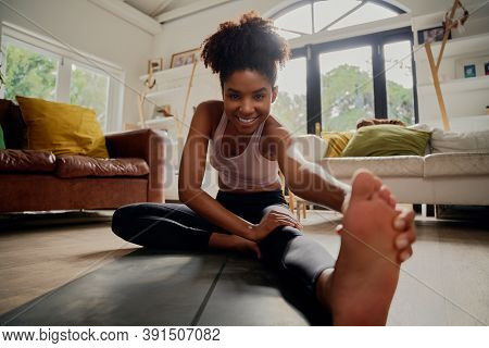 African Happy Healthy Woman In Sportswear Doing Stretching Exercise At Home On Fitness Mat During Co