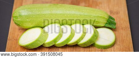Slices Of Courgettes On Wooden Chopping Board. Fresh Green Zucchini Whole And Cut Into Slices On Cut