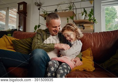 Playful Father And Daughter Tickling Each Other While Relaxing On Sofa At Home