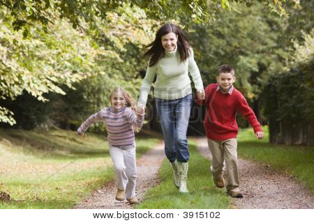Woman Running With Children Along Pathway