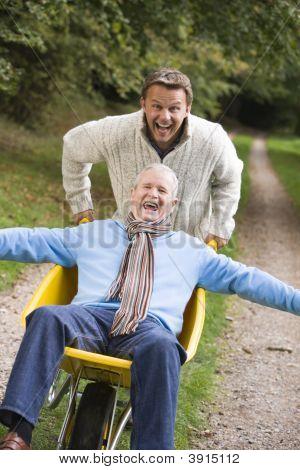 Man Pushing Father In Wheelbarrow