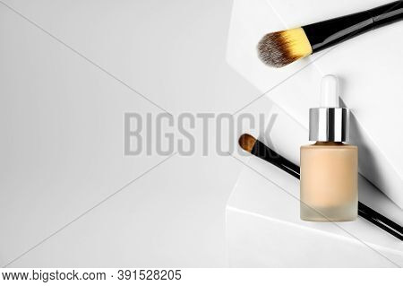 Liquid Foundation Bb Cream In A Glass Bottle With Makeup Brushes On A Geometric Background. Womens A