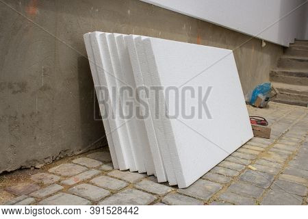 White Styrofoam Near The House, Styrofoam Sheets Stacked To The Wall For Repair And Insulation Of Th