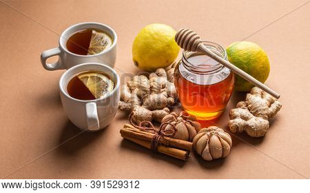 Natural Cold And Flu Home Remedies: Hot Tea Cups With Lemon, Honey, Ginger, Cinnamon And Garlic To B