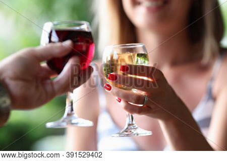Man And A Woman Are Holding Glasses Of Red And White Wine. Romantic Meetings And Dating Concept