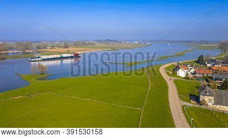 Inland Container Vessel On River Lek Aerial View Near The Village Of Ravenswaaij, Gelderland, Nether