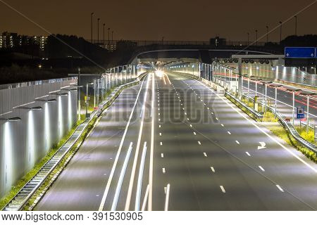 Motorway With Entrance Of Tunnel At Night With Blurred Car Lights By Long Exposure