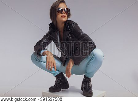 Determined fashion model looking away while wearing leather jacket and sunglasses, crouching on gray studio background