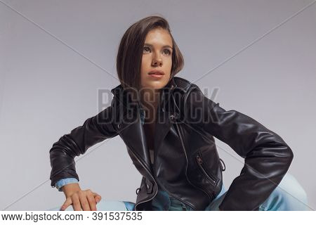 Young fashion model looking away while wearing leather jacket, crouching on gray studio background
