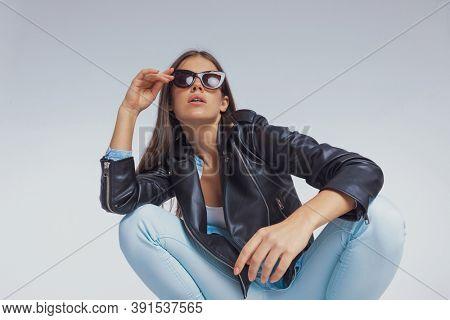Beautiful fashion model adjusting sunglasses and wearing leather jacket, crouching on gray studio background