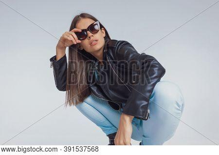 Young fashion model adjusting sunglasses while wearing leather jacket, crouching on gray studio background