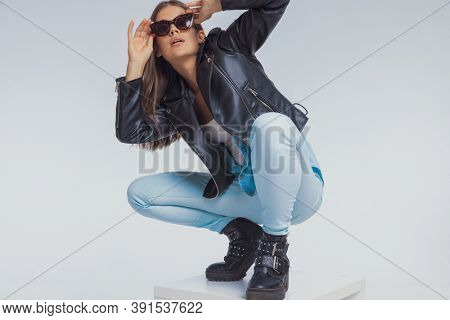 Cool fashion model fixing her sunglasses while wearing leather jacket, crouching on gray studio background