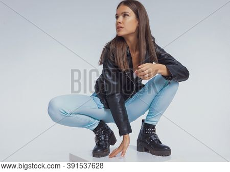 Focused fashion model looking away, wearing leather jacket while crouching on gray studio background
