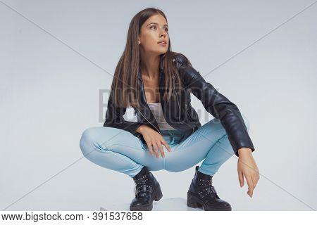 Thoughtful fashion model looking away, wearing leather jacket while crouching on gray studio background