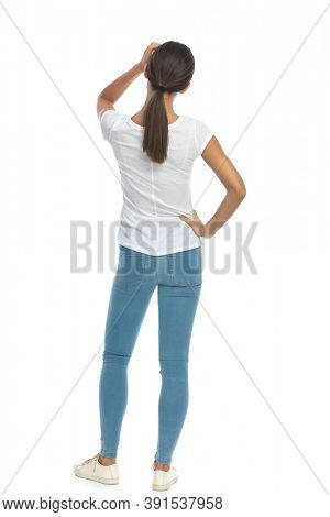 Back view of casual woman holding hands on head, waiting while standing on white studio background