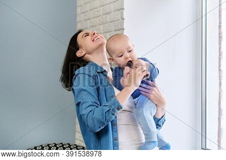 Portrait Of Happy Laughing Mother With Her Toddler Son In Her Arms. Boy Tries To Bite The Phone, The