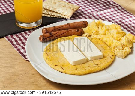 Tasty Traditional Breakfast In Colombia; Arepa Of Yellow Corn With Cheese, Scrambled Eggs And Sausag