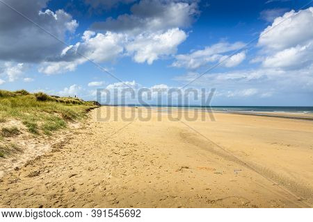 Wide Shot Of Beautiful Beach With Gold Sand And Clear Blue Water In Background Under A Blue Cloudy S