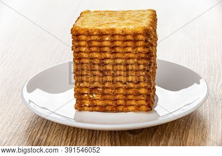 Stack Of Crunchy Cookies With Sesame In White Saucer On Wooden Table