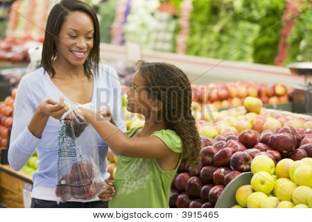 Woman And Child Choosing Fruit In Shop