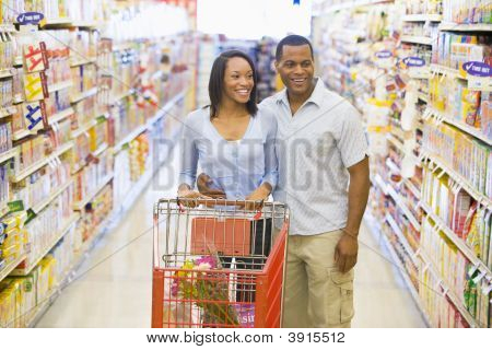 Couple Pushing Trolley In Supermarket