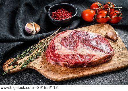 Raw Fresh Meat Ribeye Steak With Seasoning On Cutting Board. Rib Eye Beef Steak. Black Background. T