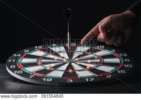 Businessman Hand In Black Suite Pointing Black Dart On Center Of Target Board On Vintage Table Meani
