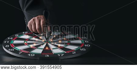 Businessman Hand In Black Suite Holding Black Dart Put To Center Of Target Board On Vintage Table Me