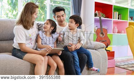 Happy Asian Family Teaching Children Son And Daughter How To Use Tablet While Sitting On Grey Sofa I