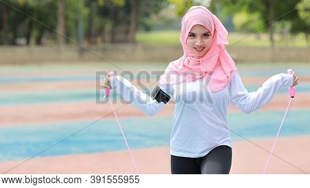 Athletic Young Asian Muslim Woman In Sportswear Standing And Skipping Rope Outdoor For Morning Exerc