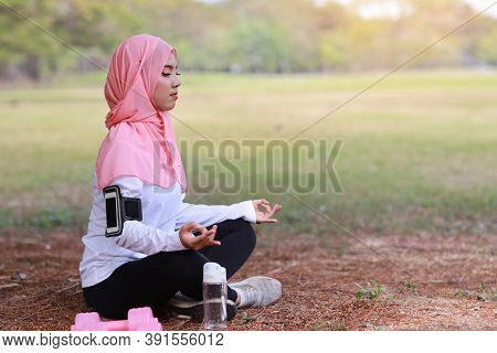 Side View Young Asian Muslim Woman Sitting On Grass, Enjoying Meditation. Peaceful Girl In Sportswea