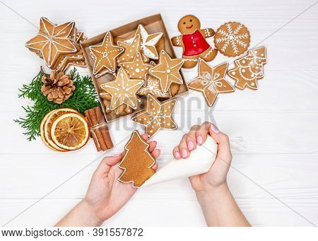 Woman Hands Paint Ornaments On Xmas Treats. Christmas Preparations. Hands Decorate Handmade Christma