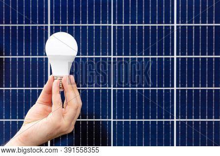 Solar Panels. Hand Holding White Bulb Against Solar Panel, Solar Station. Idea Concept Of Alternativ