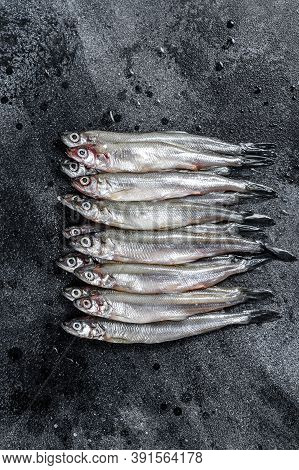 Fresh Raw Sea Small Fish Smelt. Black Background. Top View