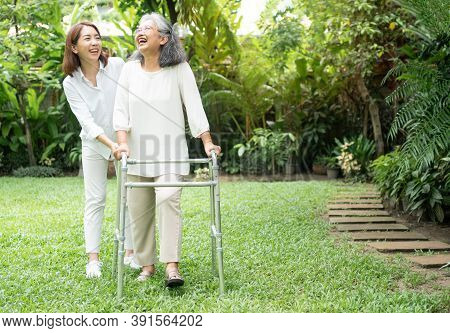 An Old Elderly Asian Woman Uses A Walker And Walking In The Backyard With Her Daughter.  Concept Of