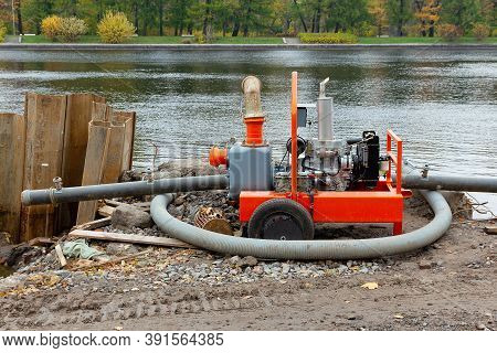Diesel Motor Pump For Pumping Water On The River Bank. Construction Works To Strengthen The Banks Us