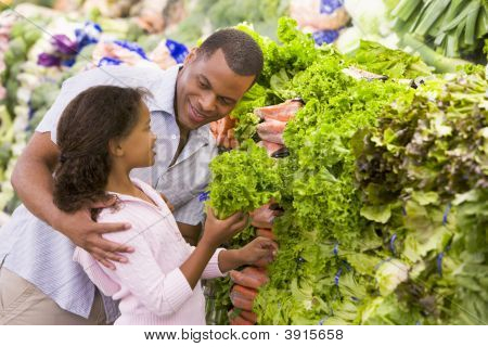 Father And Child Choosing Vegetables From Shop