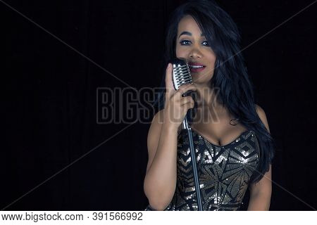 Beautiful And Sexy Black Singer In A Silver Fitted Dress With A Retro Style Of The 50s