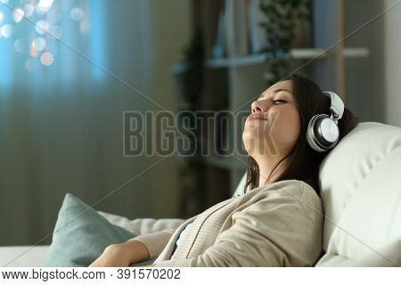 Relaxed Woman Sitting On A Sofa Listening To Music In The Night At Home