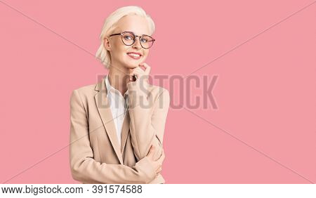 Young blonde woman wearing business clothes and glasses looking confident at the camera with smile with crossed arms and hand raised on chin. thinking positive.