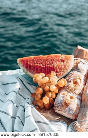 Summer Picnic Time On A Beach. Fresh Watermelon, French Baguette And Grapes On Blanket