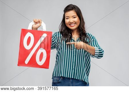 sale, outlet and consumerism concept - happy asian young woman with percentage sign on red shopping bag over grey background