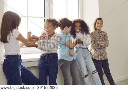 Active Group Of Multiethnic Children Have Fun Together And Tickle Each Other Standing By The Window.
