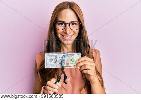 Young brunette woman cutting dollars with scissors for currency devaluation smiling with a happy and cool smile on face. showing teeth.